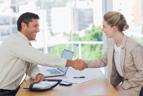 Blonde woman shaking hands while having an interview in office 2019